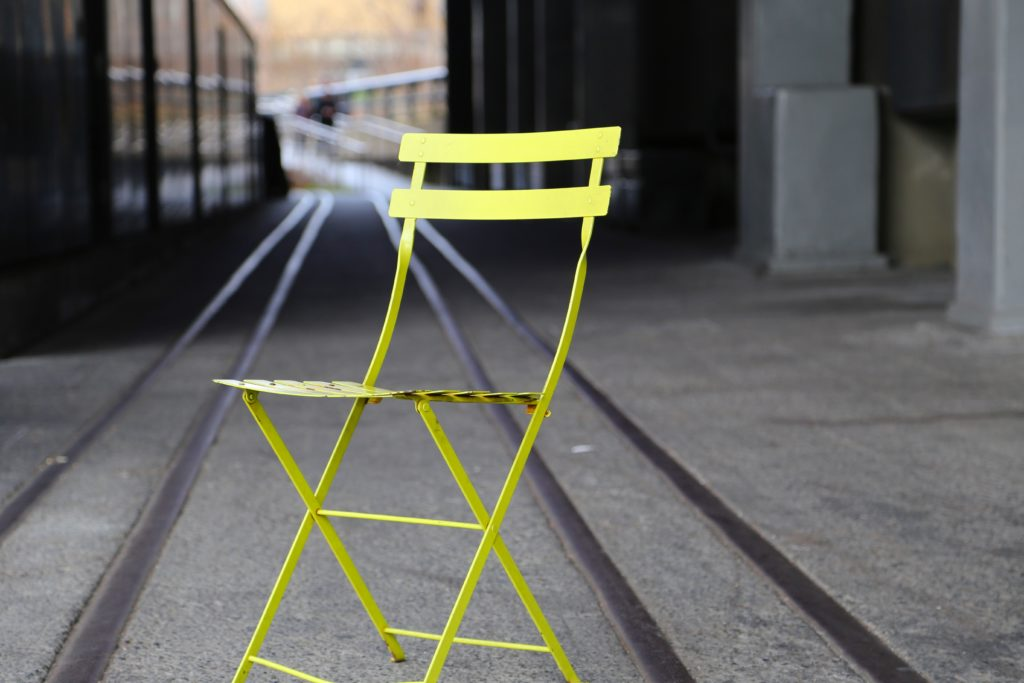 lime green cafe chair out on some tram tracks