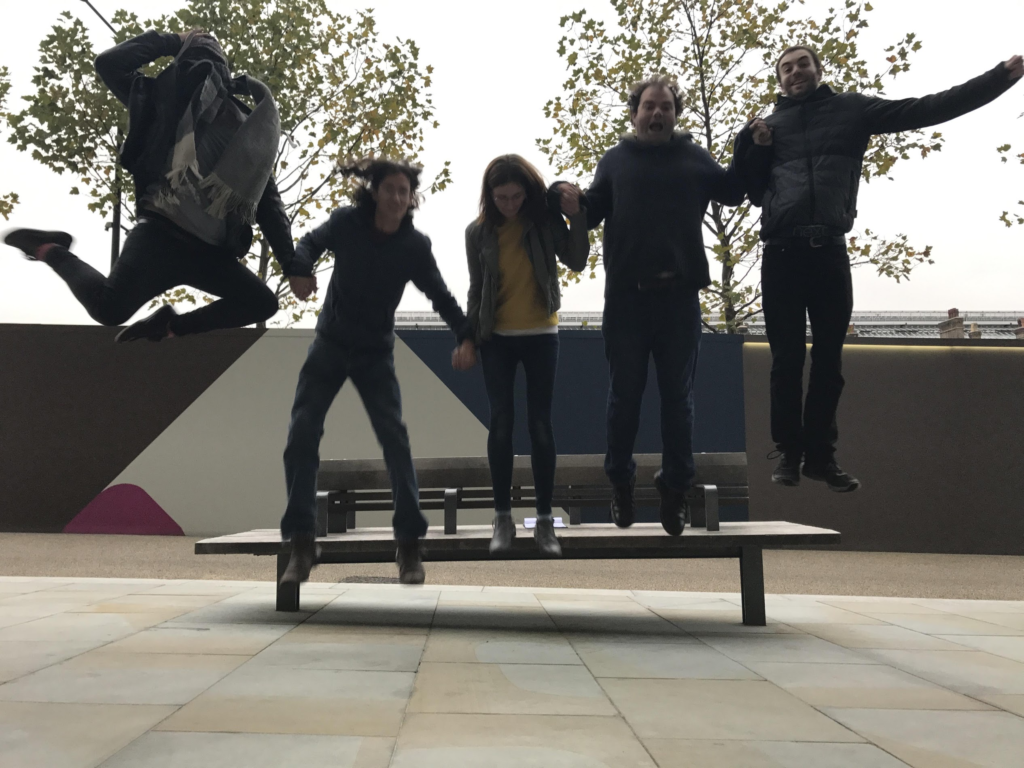 Mateus, Joaquim, Abi, Harry and Sam jumping up in the air in front of a bench