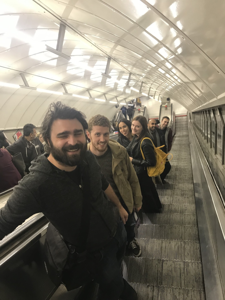 6 people looking up the escalators in an underground station smiling at the camera